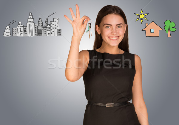 Woman making choice between city and country, holding keys in her hand Stock photo © cherezoff