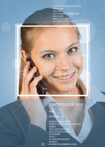 Concept of person identification. Woman using phone, smiling. Face with lines Stock photo © cherezoff
