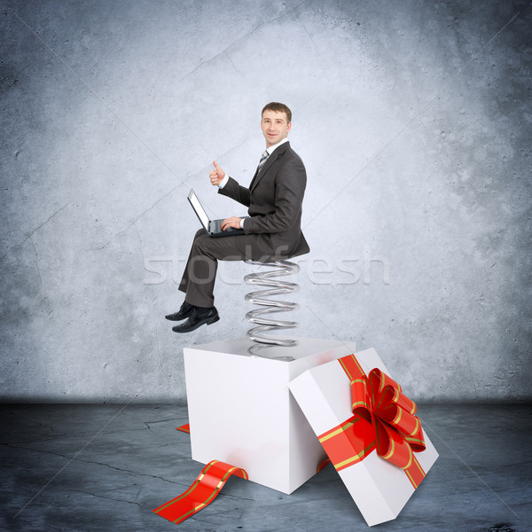 Businessman with laptop sitting on coil spring Stock photo © cherezoff