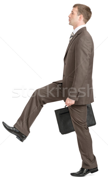 Stock photo: Businessman making large step with suitcase