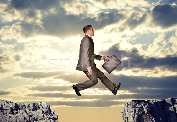 Businessman hopping over abyss Stock photo © cherezoff