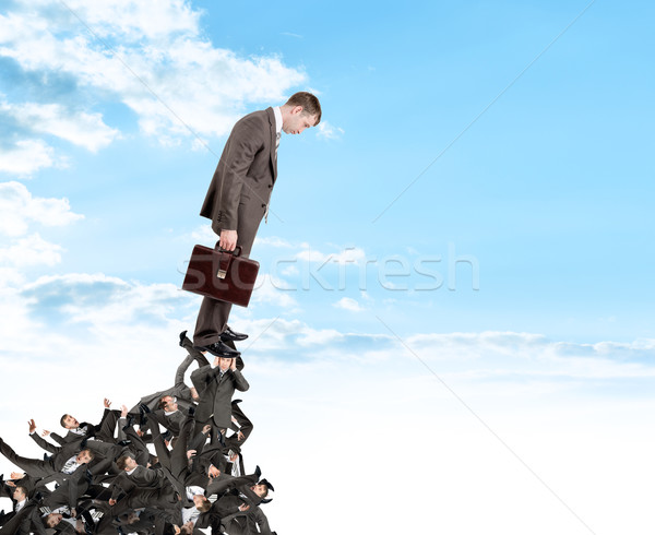 Businessman looking down from pile of people Stock photo © cherezoff