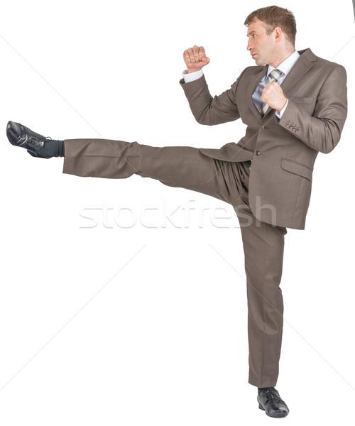 Angry businessman kicking Stock photo © cherezoff