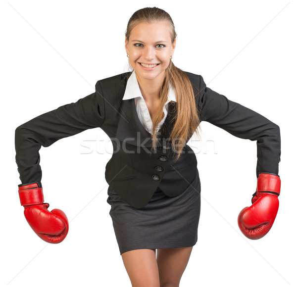 Businesswoman wearing boxing gloves bending forward with her arms bent and outstretched Stock photo © cherezoff
