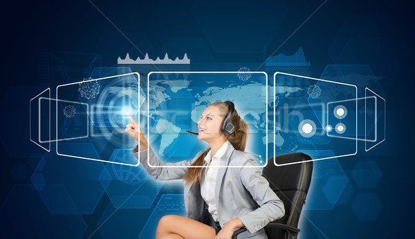 Businesswoman in headset using touch screen interfaces Stock photo © cherezoff