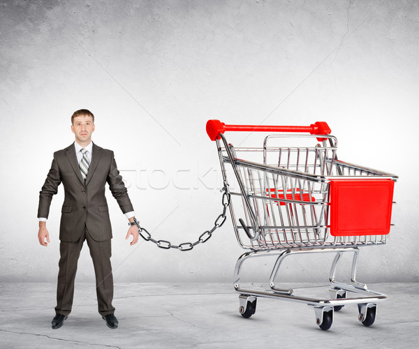 Businessman chained to shopping cart Stock photo © cherezoff