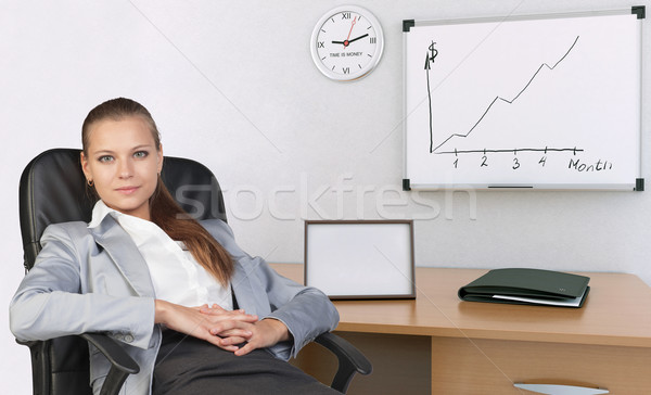 Businesswoman in office chair, with her hands clasped over stomach Stock photo © cherezoff