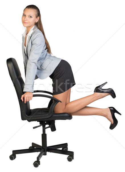 Businesswoman kneeling on office chair, looking at camera cheerfully Stock photo © cherezoff