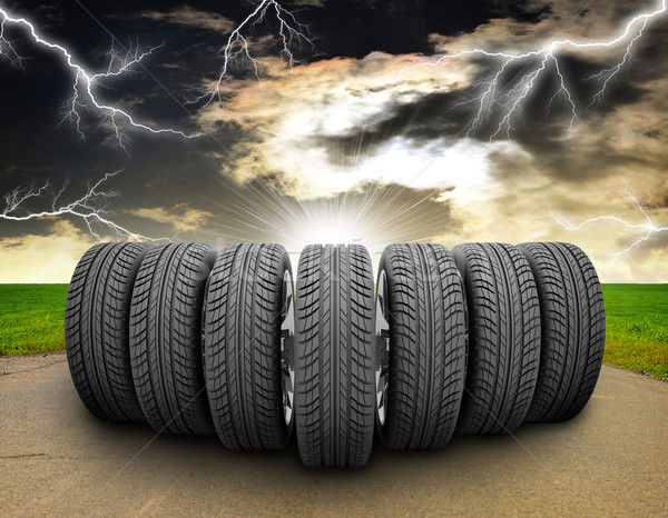 Wedge of car wheels. Road, roadsides, grass field and stormy sky in background Stock photo © cherezoff