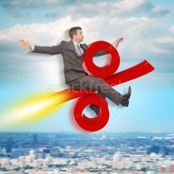 Businessman flying on percent sign Stock photo © cherezoff