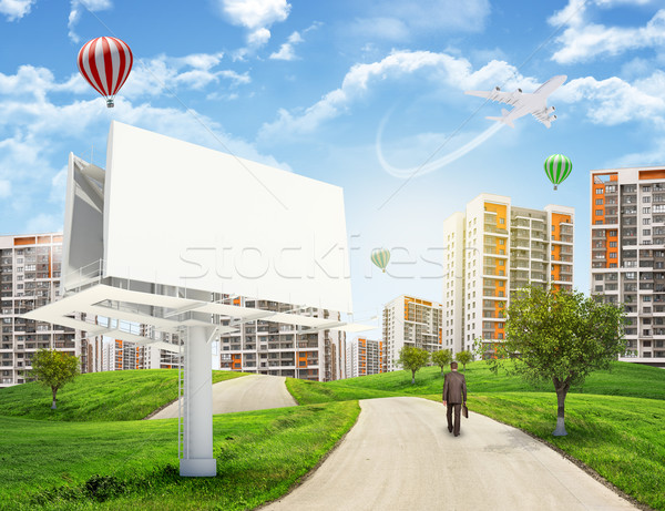 Stock photo: Businessman walks on road. Rear view. Buildings, grass field, large billboard and sky in background