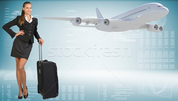 Businesswoman with suitcase. Image of flying airliner beside Stock photo © cherezoff