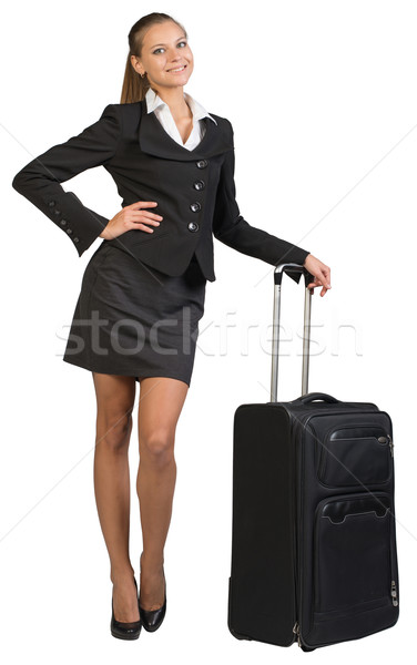 Businesswoman with wheeled travel bag, hand on hip Stock photo © cherezoff