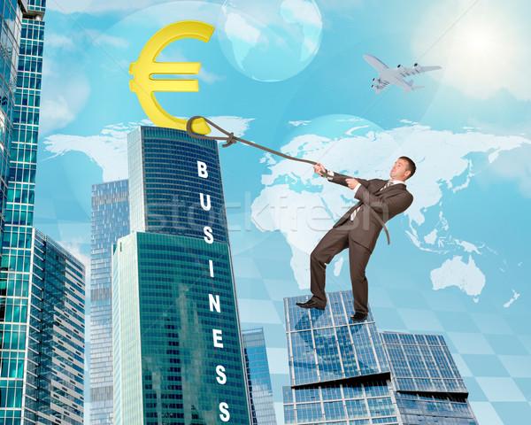 Hombre escalada rascacielos euros signo empresario Foto stock © cherezoff