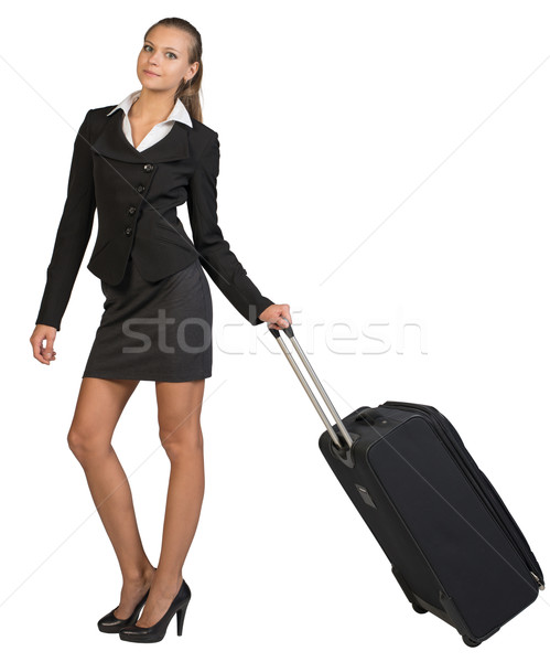 Businesswoman holding wheeled bag in moving position Stock photo © cherezoff