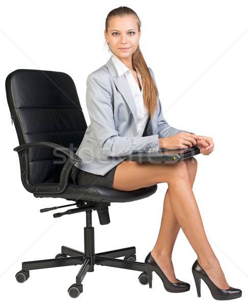 Businesswoman on office chair, holding closed laptop Stock photo © cherezoff