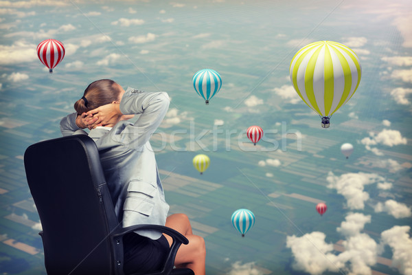 Businesswoman sitting with her hands clasped behind head against aerial view background Stock photo © cherezoff