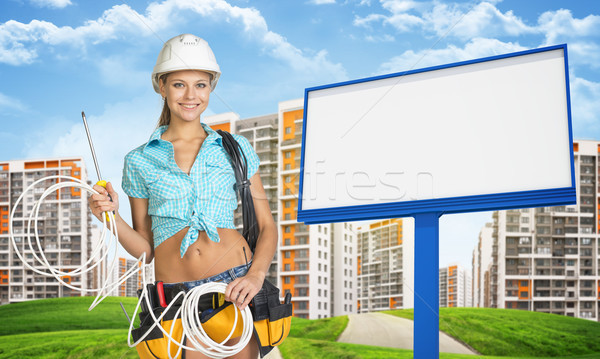 Woman in hard hat and tool belt holding coil of cable Stock photo © cherezoff