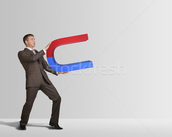 Businessman in suit holding big magnet Stock photo © cherezoff