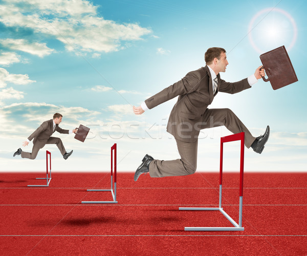 Businessmen hopping over treadmill barrier Stock photo © cherezoff