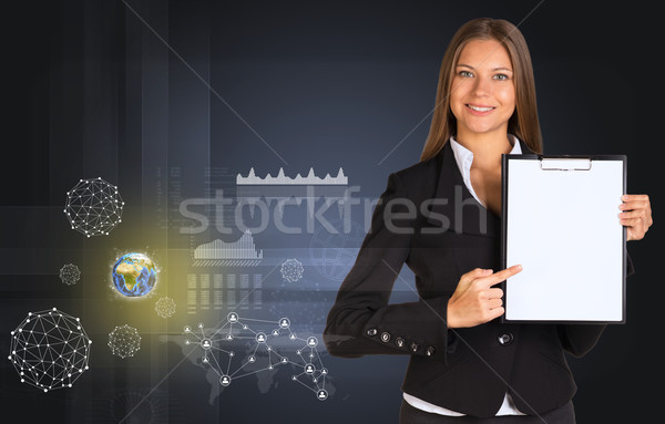 Beautiful businesswoman holding paper holder. Earth, network and graphs Stock photo © cherezoff