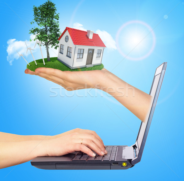 White shack in hand with red roof and chimney of screen laptop. Background sun shines brightly on ri Stock photo © cherezoff