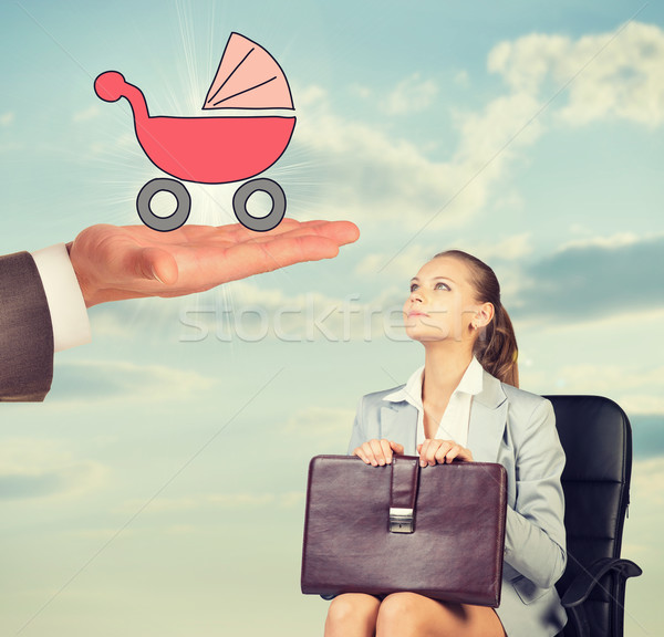 Young woman sitting in chair and looking up at baby carr Stock photo © cherezoff