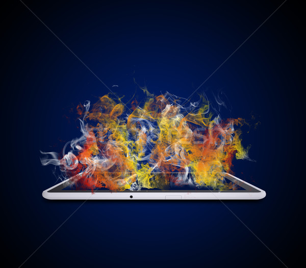 Stock photo: Tablet pc emits colored smoke