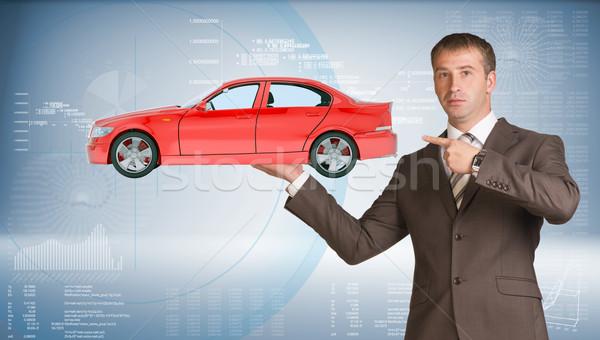 Businessman holding car Stock photo © cherezoff