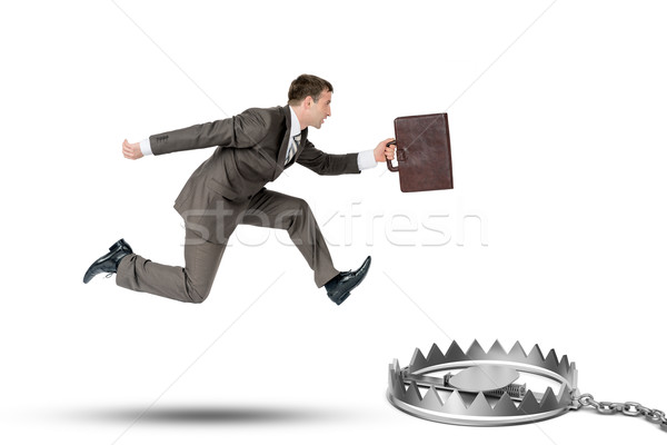 Running businessman with bear trap Stock photo © cherezoff
