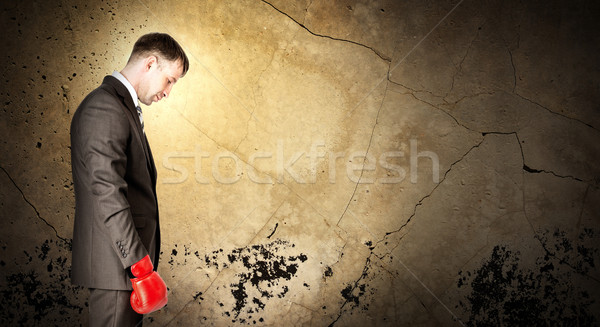 Stock photo: Businessman wearing boxing gloves and looking sad