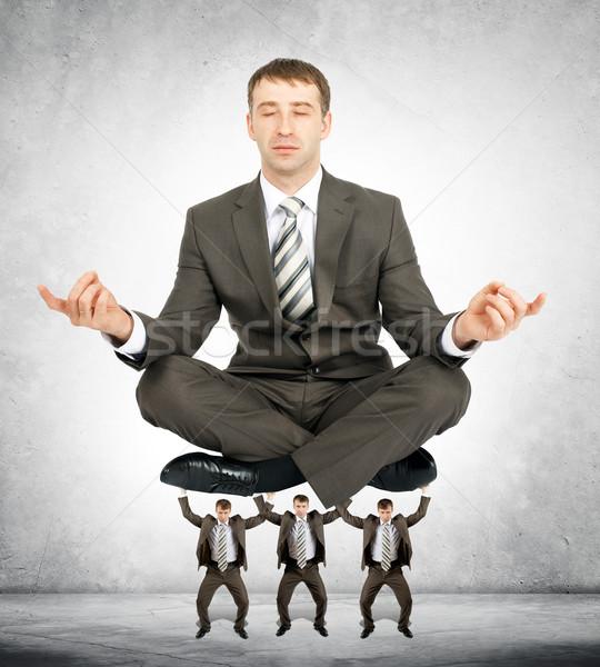 Giant business man sitting on little men  Stock photo © cherezoff
