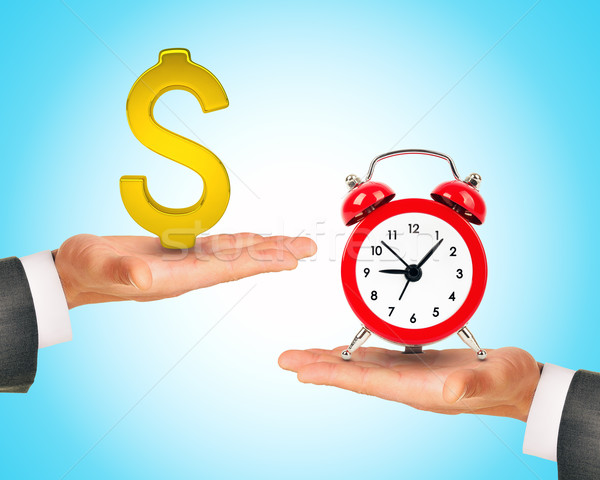 Hand with dollar sign and alarm clock on another  Stock photo © cherezoff