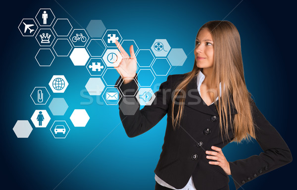 Beautiful businesswoman in suit presses finger on virtual icon. Hexagons with icons Stock photo © cherezoff