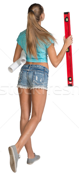 Pretty woman holding paper scrolls and red building level. Full length. Rear view Stock photo © cherezoff