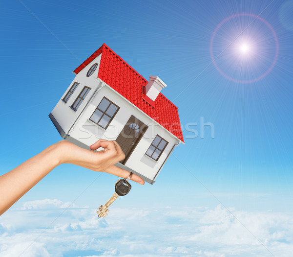 White house and keys in hand with red roof, brown door, chimney. Background sun shines brightly Stock photo © cherezoff