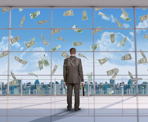 Businessman looking at money Stock photo © cherezoff