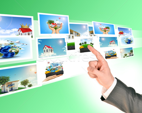 Businessmans arm touching holographic pictures Stock photo © cherezoff