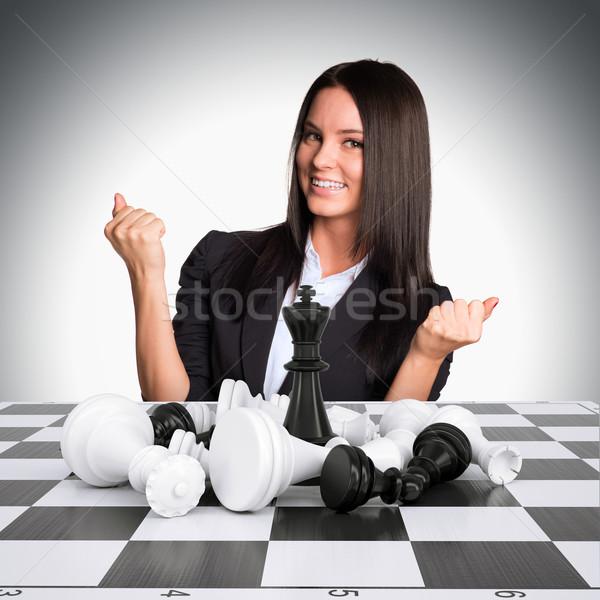 Joyful businesswoman wins chess and raised his hands up Stock photo © cherezoff