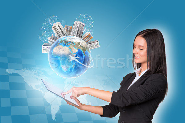 Women using digital tablet. Earth with buildings Stock photo © cherezoff