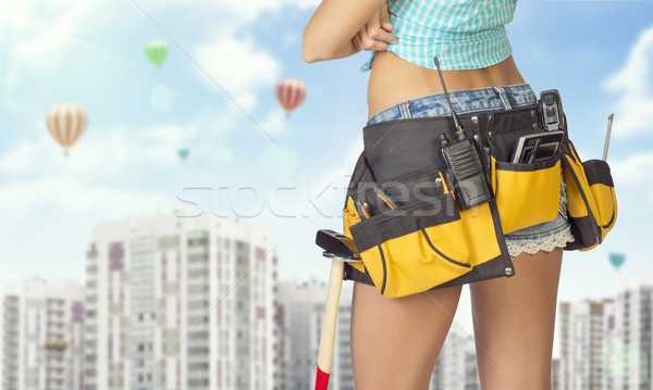 Woman in tool belt standing backwards. Cropped image. High-rise buildings as backdrop Stock photo © cherezoff