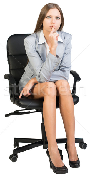 Businesswoman on office chair holding finger to her lips Stock photo © cherezoff
