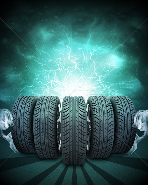 Wedge of new car wheels. Green background is night sky and stripes at bottom Stock photo © cherezoff
