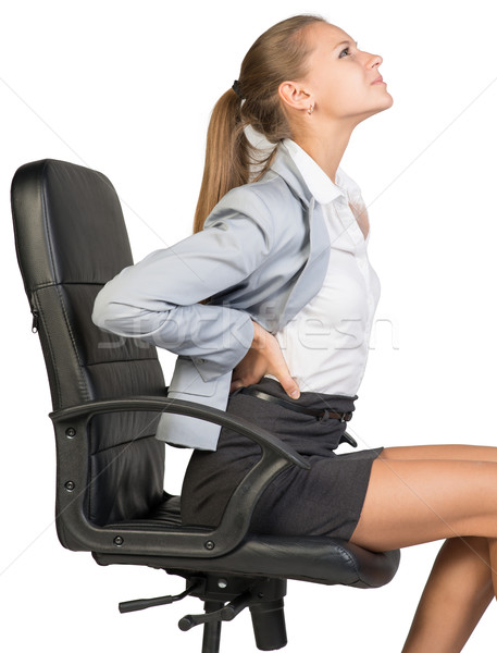 Businesswoman with lower back pain from sitting on office chair Stock photo © cherezoff