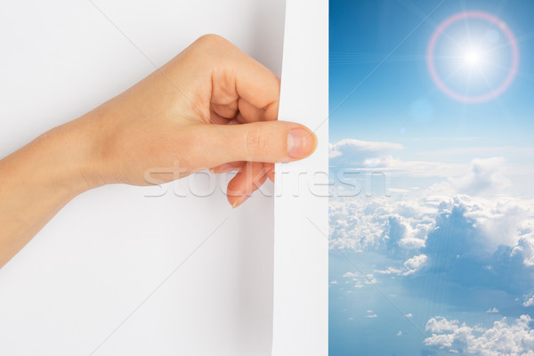Hand turning the page revealing blue skies Stock photo © cherezoff
