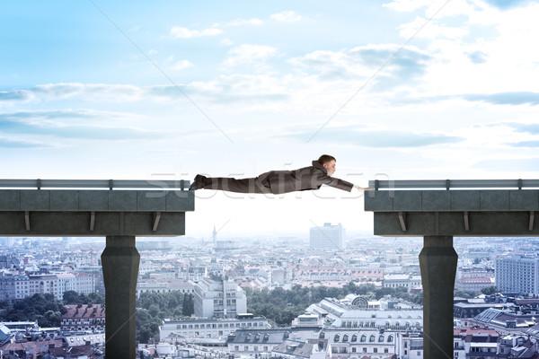 Businessman linking broken bridge Stock photo © cherezoff