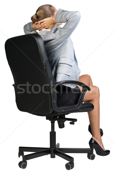 Businesswoman sitting back in chair with hands clasped behind her head Stock photo © cherezoff
