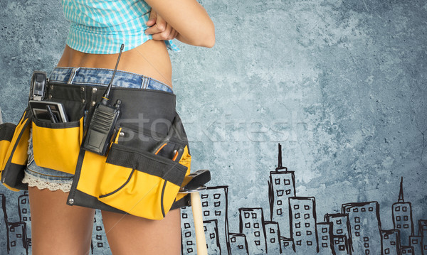 Woman in tool belt against stone wall with sketch of city on it Stock photo © cherezoff