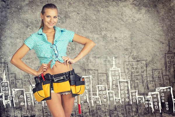 Woman in tool belt standing akimbo against stone wall with sketch of city on it Stock photo © cherezoff