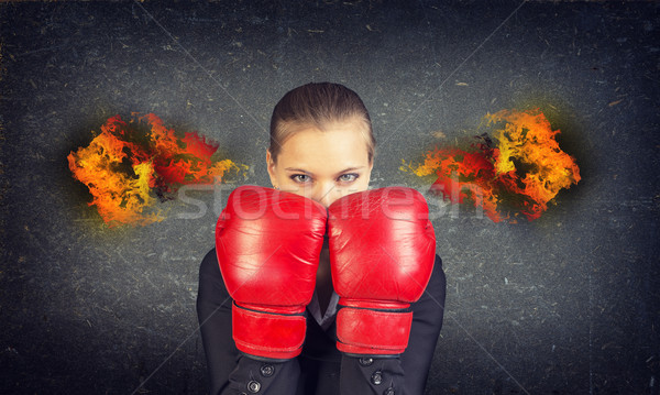 Woman boxing gloves covers her face. Fire from ears. Concrete gray wall as backdrop Stock photo © cherezoff